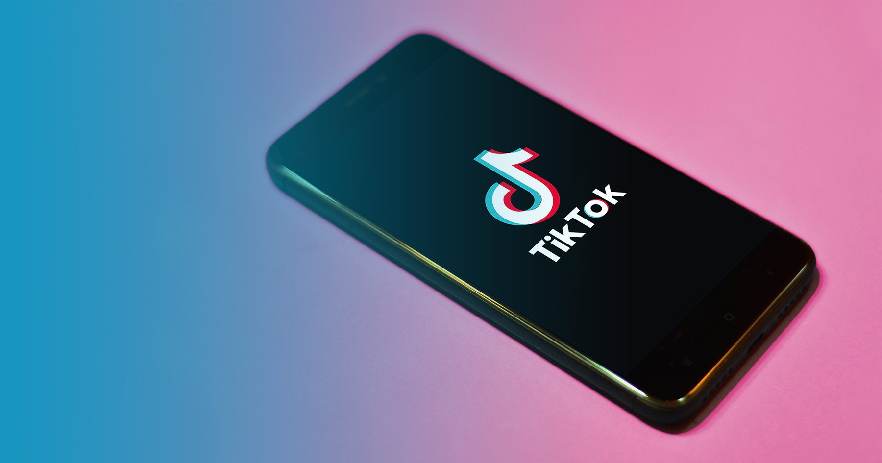 Phone with TikTok app open on a pink background