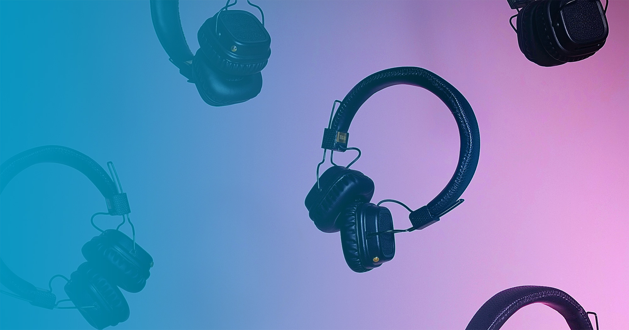 Multiple headphones floating on pink background