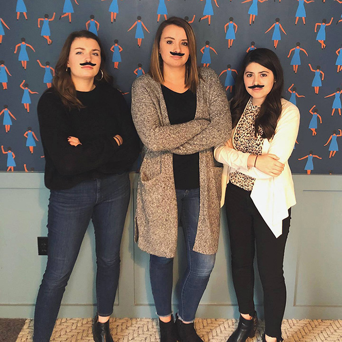 Fun photo of coworkers with stick on mustaches