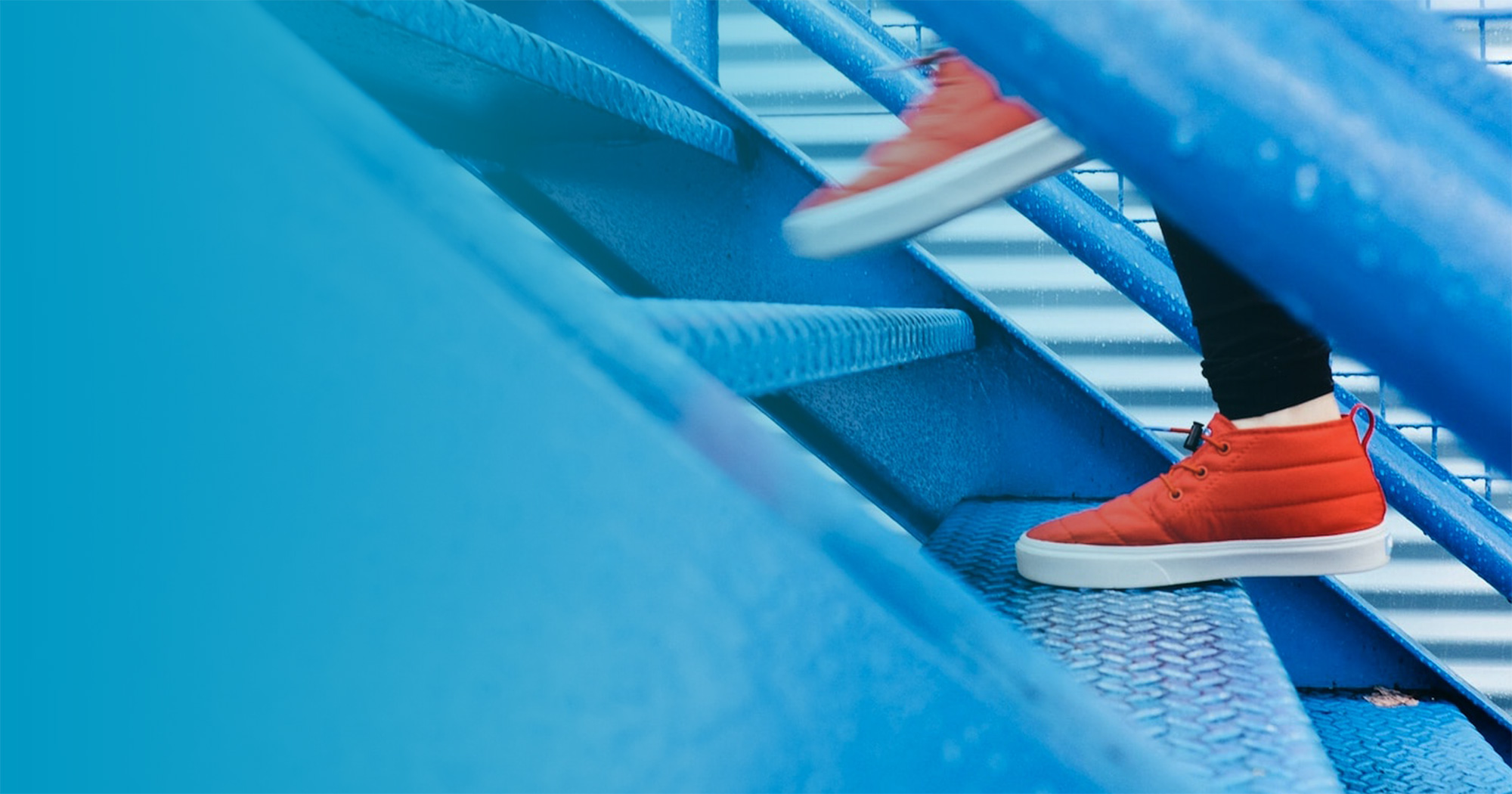 Person with orange sneakers climbing up a blue metal staircase