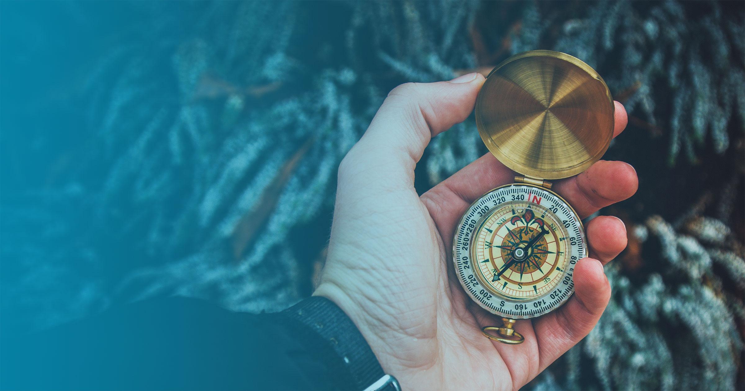 Hand holding brass compass