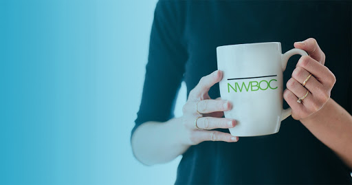 Woman holding a coffee cup with the NWBOC badge on it